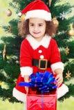 在圣诞树附近的小女孩与一件礼物在它的手上 库存图片