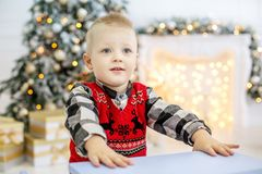 在圣诞树附近的小男孩 概念愉快的圣诞节,新的Y 免版税库存图片