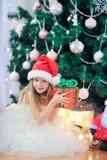 在圣诞树附近的小逗人喜爱的女孩 孩子在与礼物盒的圣诞树下 免版税库存照片
