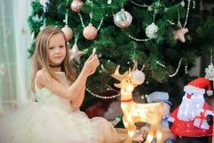 在圣诞树附近的小逗人喜爱的女孩 孩子在与礼物盒的圣诞树下 库存图片