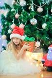 在圣诞树附近的小逗人喜爱的女孩 孩子在与礼物盒的圣诞树下 图库摄影