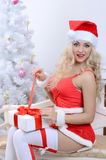 在圣诞树附近的微笑的圣诞老人妇女 免版税库存照片