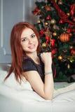 在圣诞树附近的微笑的妇女 免版税库存照片