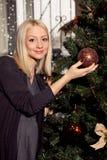 在圣诞树附近的怀孕的白肤金发的妇女 免版税库存图片