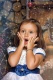 在圣诞树附近的惊奇的小女孩 免版税图库摄影