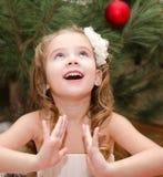 在圣诞树附近的愉快的可爱的小女孩 免版税库存图片