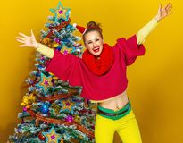 在圣诞树附近的愉快的妇女在黄色背景欣喜 免版税库存照片