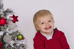 在圣诞树附近的愉快的孩子 免版税库存照片