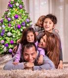 在圣诞树附近的愉快的家庭 免版税库存照片