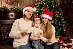 在圣诞树附近的愉快的微笑的家庭庆祝新年 库存照片