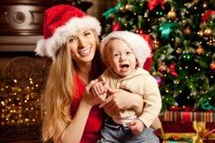 在圣诞树附近的愉快的微笑的家庭庆祝新年 图库摄影