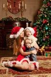 在圣诞树附近的愉快的微笑的家庭庆祝新年 免版税库存图片