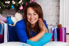 在圣诞树附近的愉快的年轻深色的妇女开头礼物盒 免版税库存照片