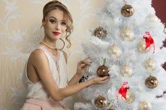 在圣诞树附近的时尚妇女 免版税库存照片