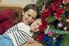 在圣诞树附近的母亲和儿子 免版税库存照片