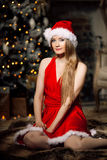 年轻在圣诞树附近的秀丽微笑的圣诞老人妇女 Fashio 免版税图库摄影