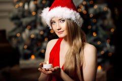年轻在圣诞树附近的秀丽微笑的圣诞老人妇女 Fashio 库存照片