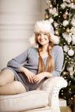年轻在圣诞树附近的秀丽微笑的圣诞老人妇女 Fashio 免版税库存照片