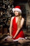 年轻在圣诞树附近的秀丽微笑的圣诞老人妇女 Fashio 免版税库存图片