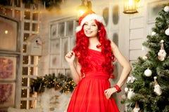 年轻在圣诞树附近的秀丽微笑的圣诞老人妇女 Fashionabl 免版税库存图片