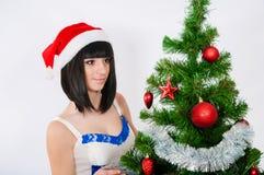 在圣诞树附近的美丽的女孩 图库摄影