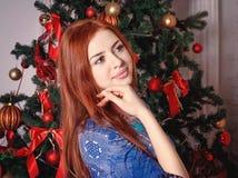 在圣诞树附近的美丽的妇女 免版税库存图片
