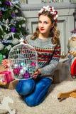 在圣诞树附近的美丽的白肤金发的女孩 免版税图库摄影
