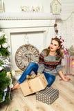 在圣诞树附近的美丽的白肤金发的女孩 免版税库存照片