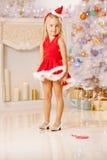 在圣诞树附近的美丽的矮小的圣诞老人女孩 愉快的gir 图库摄影