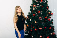 在圣诞树附近的美丽的金发碧眼的女人 图库摄影