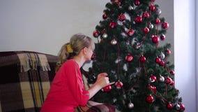在圣诞树附近的美丽的金发碧眼的女人 影视素材
