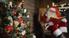 在圣诞树附近的被弄脏的圣诞老人举行老红色丝绸册页与玩具和光 股票录像