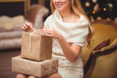 在圣诞树附近的金发碧眼的女人 图库摄影