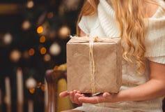在圣诞树附近的金发碧眼的女人 免版税库存照片