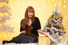 在圣诞树附近的长的头发妇女打开礼物 库存图片