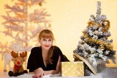 在圣诞树附近的长的头发妇女打开礼物 免版税库存图片