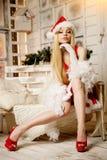 在圣诞树附近的年轻秀丽圣诞老人妇女 时兴的lu 库存图片
