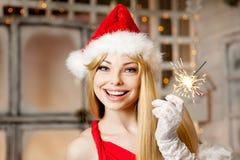 在圣诞树附近的年轻秀丽圣诞老人妇女 时兴的lu 库存照片