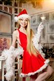 在圣诞树附近的年轻秀丽圣诞老人妇女 时兴的lu 免版税图库摄影