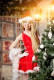 在圣诞树附近的年轻秀丽圣诞老人妇女 时兴的lu 免版税库存照片
