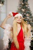 在圣诞树附近的年轻秀丽圣诞老人妇女 时兴的lu 免版税库存图片