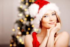 在圣诞树附近的年轻美丽的微笑的圣诞老人妇女 启远地 免版税库存照片