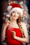 在圣诞树附近的年轻美丽的微笑的圣诞老人妇女 启远地 库存照片