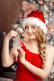 在圣诞树附近的年轻美丽的微笑的圣诞老人妇女 启远地 免版税图库摄影