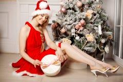 在圣诞树附近的年轻美丽的微笑的圣诞老人妇女 启远地 免版税库存图片