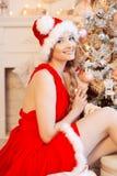 在圣诞树附近的年轻美丽的微笑的圣诞老人妇女 启远地 库存图片