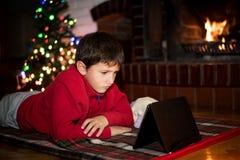 在圣诞树a旁边的男孩观看的片剂 免版税库存图片