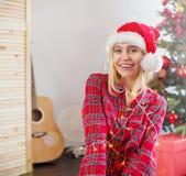 在圣诞灯包裹的愉快的妇女 免版税库存照片