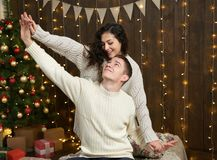 在圣诞灯和装饰的夫妇,穿戴在白,女孩和人,在黑暗的木背景,冬天holida的杉树 免版税图库摄影
