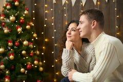在圣诞灯和装饰的夫妇,穿戴在白,女孩和人,在黑暗的木背景,冬天holida的杉树 免版税库存照片